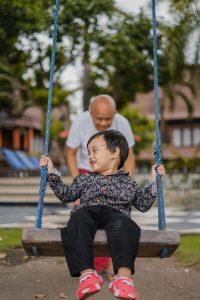 Junge mit Opa auf Schaukel